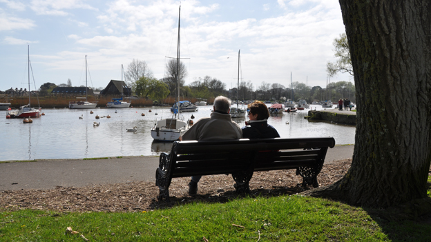 Couple sitting no bench looking at boats