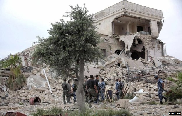 Government forces search for survivors in the remains of a hotel in Aleppo's Old City destroyed by an explosion on 8 May 2014