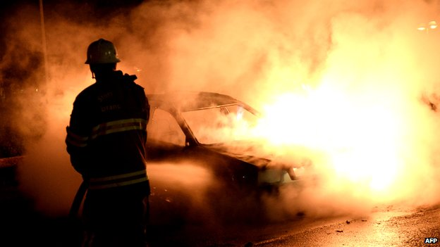 A car burns during riots in the Stockholm suburb of Kista in May 2013
