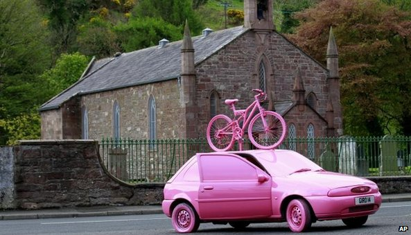 A car and bicycle is painted pink in the village of Cushendall