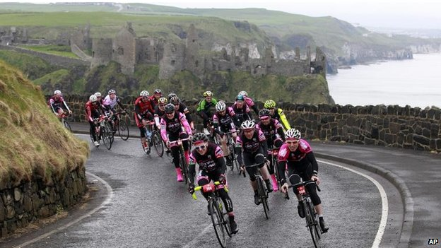 Cyclists pass Dunluce Castle