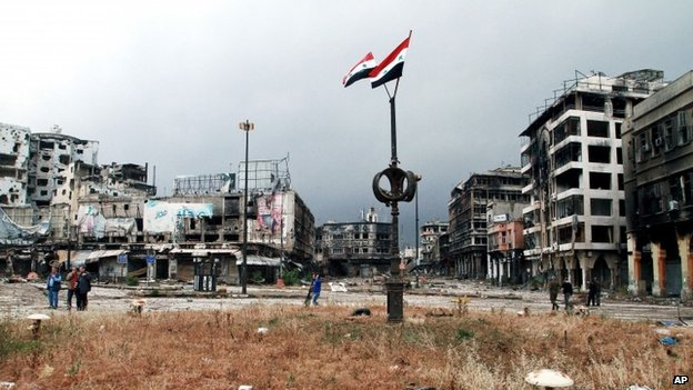 Syrian flags fly from a pole in the Old City of Homs (8 May 2014)