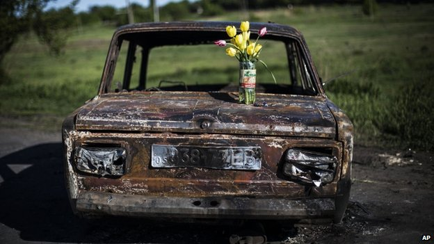 A bouquet of flowers stands on a burned car at the site of clashes between pro-Russia gunmen and the Ukrainian army, north of Sloviansk,, 7 May