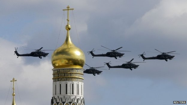 Military helicopters fly in formation during rehearsals for the Victory Day military parade