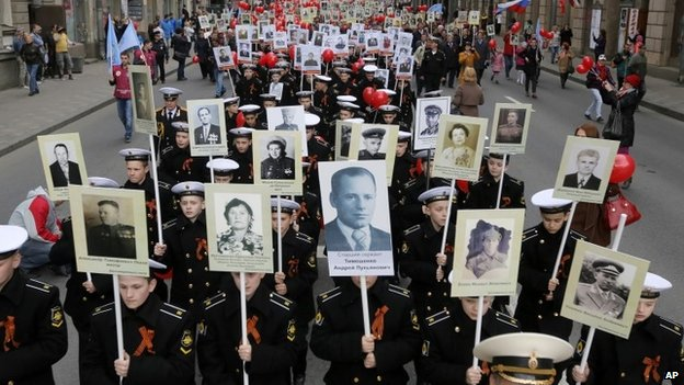 Navy cadets and local residents carry portraits of their relatives, veterans of World War Two as they celebrate upcoming Victory Day in St Petersburg