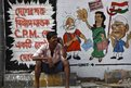 A man speaks on his mobile phone in front of graffiti depicting Indian political figures on a wall ahead of the general election in Calcutta.