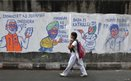 A school girl walks past a wall with graffiti depicting Indian politics in Calcutta.