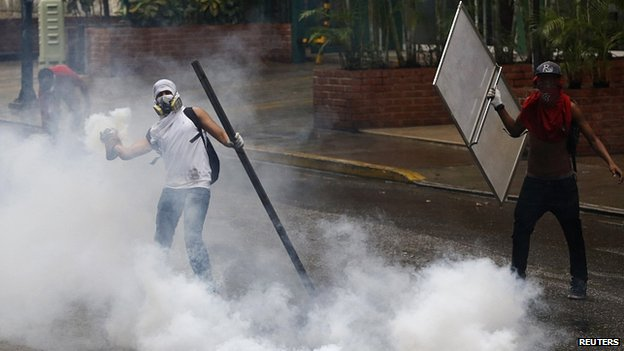 Protesters throw tear gas canisters back at police in Caracas. 8 May 2014