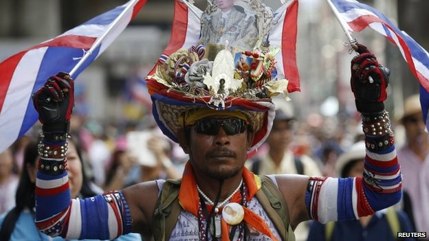An anti-government protester wears a hat with a picture of Thailand's King Bhumibol Adulyadej as he joins thousands of others marching through central Bangkok 9 May 2014