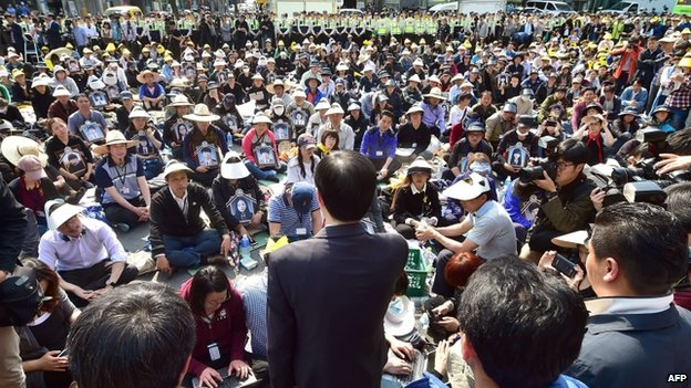 South Korea's state-funded broadcast KBS President Gil Hwan-Young (lower C) makes an apology to relatives of victims of the sunken South Korean ferry Sewol as they stage a sit-in protest on a street near the presidential Blue House in Seoul on 9 May 2014