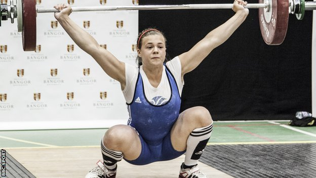 Rebekah Tiler hoists weights above her head with her knees bent