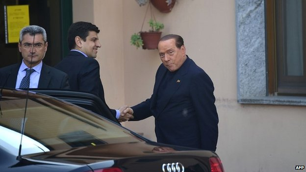 Silvio Berlusconi shakes hands with an official from the care home as he arrives to start his community service - 9 May 2014