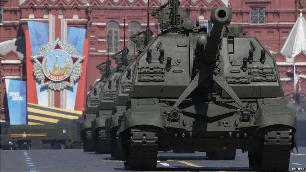 Russian servicemen onboard self-propelled artillery vehicles salute during the Victory Day Parade in Moscow's Red Square, 9 May 2014