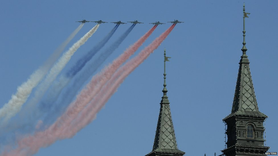 Russian military aircraft trail smoke in the colours of the Russian tricolour above the Victory Day Parade in Moscow's Red Square, 9 May 2014