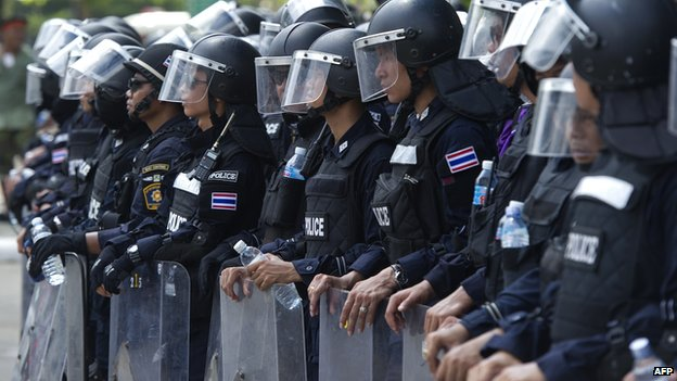 Thai policemen stand guard at the entrance of a television station during an anti-government rally in Bangkok on 9 May.