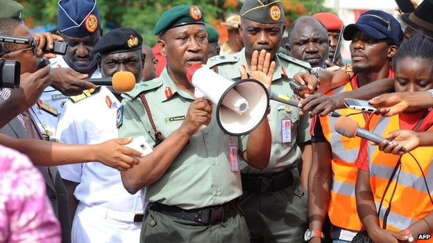 "Defence spokeman Major General Chris Olukolade speaks to a crowd in Abuja protesting over the government's ""indifference"" to the mass abduction - 6 May 2014"
