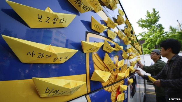 A man attaches yellow paper ships dedicated to dead and missing passengers onboard the sunken Sewol ferry, on a police bus blocking a road leading to the Presidential Blue House in Seoul, 9 May 2014