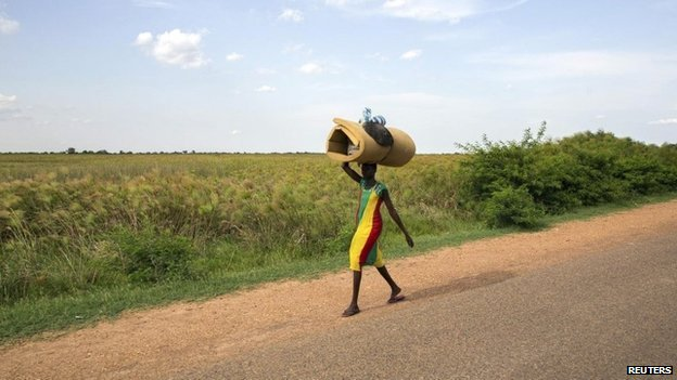 A civilian carries her belongings as she flees from renewed attacks in Bentiu, Unity state of South Sudan on 20 April 2014