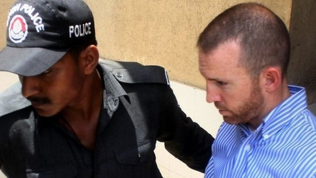 In this photograph taken on May 6, 2014 Pakistani policemen escort an alleged US FBI agent under arrest as they leave the local court in Karachi.