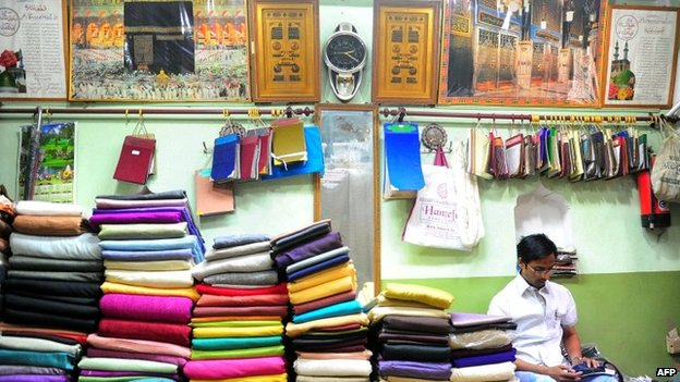 A shopkeeper sits amongst saris in Varanasi