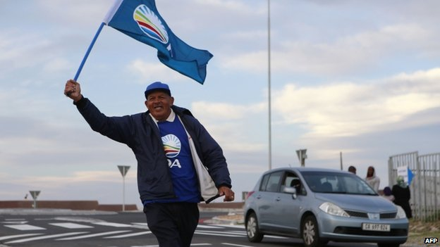 A Democratic Alliance supporter waves the party's flag outside the Colorado polling station in Mitchells Plain on the Cape Flats, South Africa, 7 May 2014