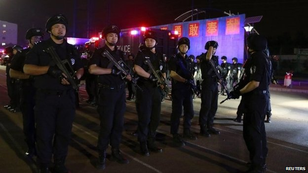 Members of the Special Weapons and Tactics (SWAT) team stand in formation as they gather during an anti-terrorism drill in Beijing, 8 May 2014