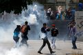 People run away from tear gas during a protest against President Nicolas Maduro's government in Caracas