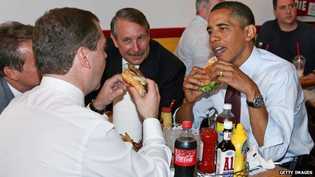 Obama eats a hamburger