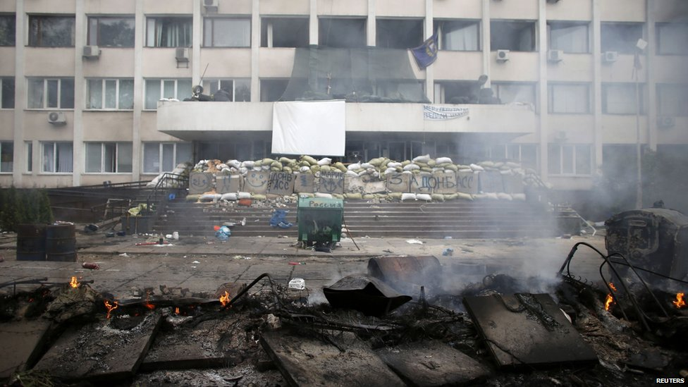 Smoke rises from burnt barricades in front of the police headquarters in the south-eastern port city of Mariupol, 9 May 2014