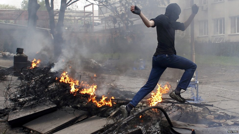 A masked man jumps over a burning barricade in front of the police headquarters in the south-eastern port city of Mariupol, 9 May 2014