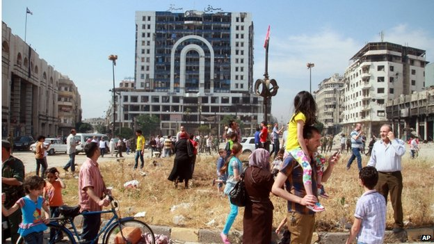 Syrian civilians walk through a city square as they return to Homs on 9 May 2014