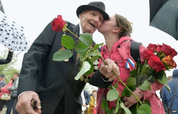 A women greets a WWII veteran as Latvia's large Russian minority gathered to mark 69 years since the end of WWII during Victory Day celebrations at the Soviet Victory Monument in Riga on May 9