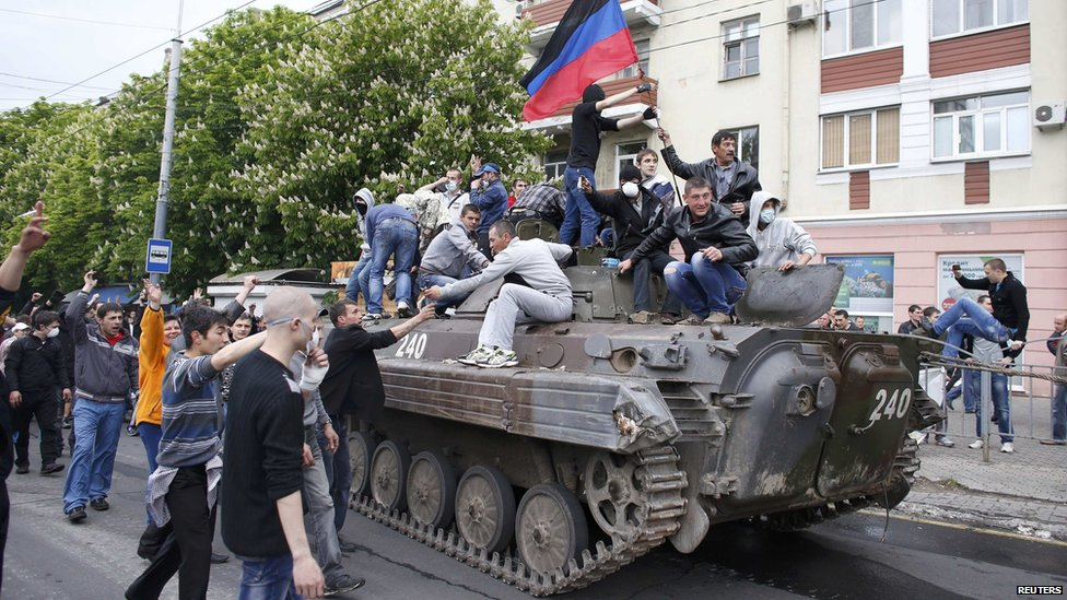 People climb a broken armoured vehicle left behind after Ukrainian forces attacked police headquarters in an attempt to drive out pro-Russian militants in Mariupol, 9 May 2014