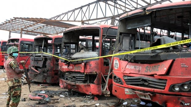A soldier standing guard in front of burnt buses after an attack blamed on Boko Haram in Abuja, Nigeria - 14 April 2014