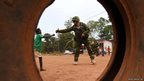 An Estonian soldier of the European Union Force in the Central African Republic (EUFOR-CAR) bumps fists with a Central African child in Bangui