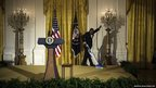 A member of staff vacuums a podium in the East Room of the White House in Washington