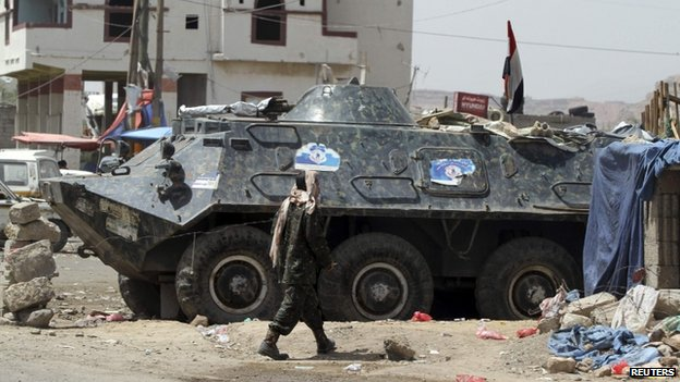 A soldier walks near an armoured military vehicle at a checkpoint to the city of Sanaa, 3 May 2014