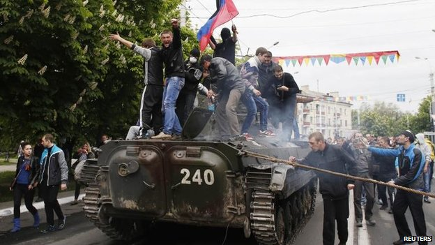 Protesters board a broken down armoured vehicle in Mariupol, 9 May