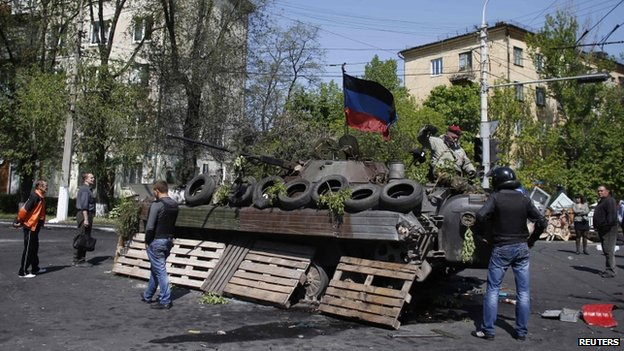 Onlookers next to an armoured peronnel carrier in Mariupol, 10 May 2014