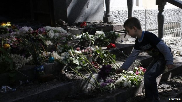A boy places flowers in front of a gutted police station building in Mariupol, eastern Ukraine 10 May 2014