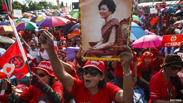 "A member of the pro-government ""red shirt"" group holds a picture of ousted Thai prime minister Yingluck Shinawatra during a rally in Nakhon Pathom province on the outskirts of Bangkok, May 10"