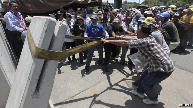 Anti-government protesters pull down a concrete barrier blocking the entrance of a police compound housing a government security group, as protesters gather outside demanding an apology from the police for firing teargas on demonstrators on Friday, in the north of Bangkok May 10