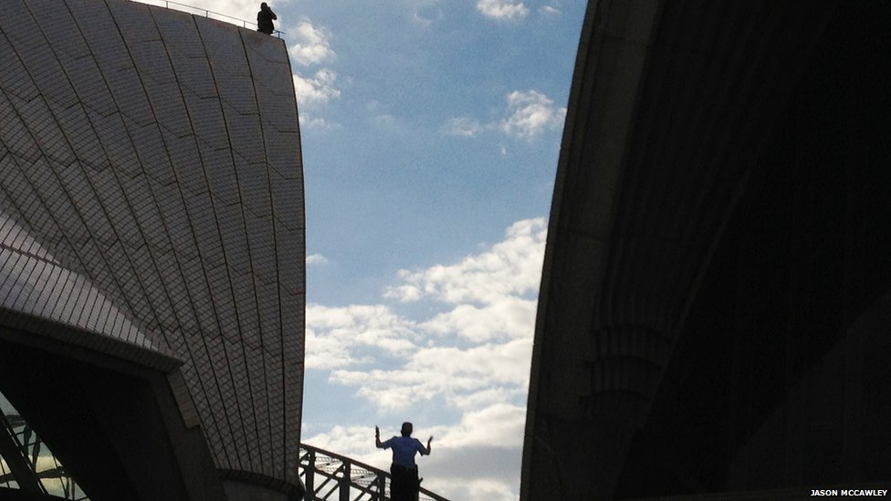 A man climbed on the sails at Sydney Opera House before being talked down by police