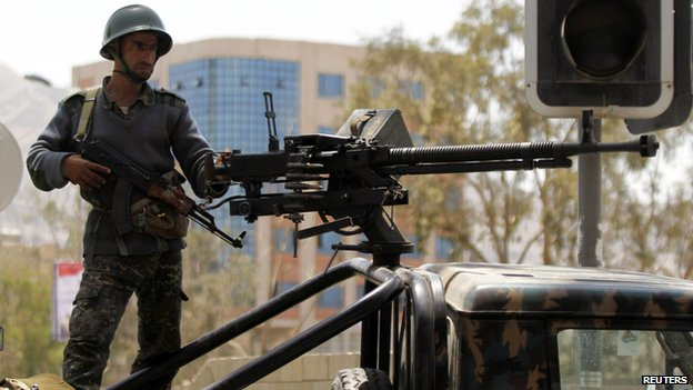 A soldier stands guard on a military vehicle at a checkpoint on a road to the city of Sanaa, May 11
