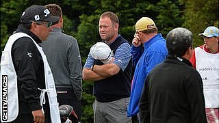 Alastair Forsyth talks to fellow golfers after the heart attack of his caddie Iain McGregor