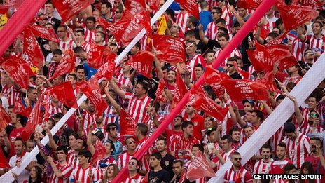 Atletico de Madrid fans wave red plastic flags supporting their team prior to start the La Liga match