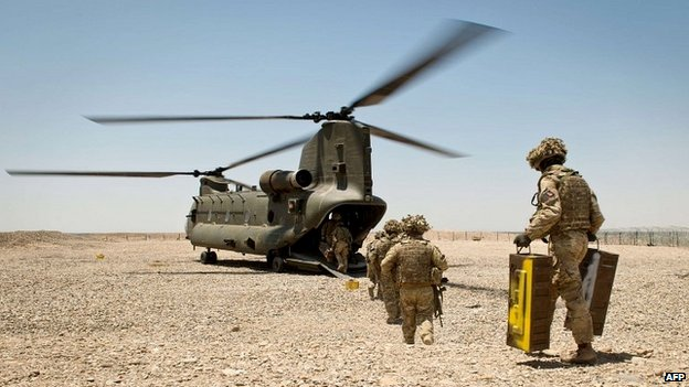 British soldiers carry equipment to a helicopter as an observation post in Helmand Province closes - 10 May 2014