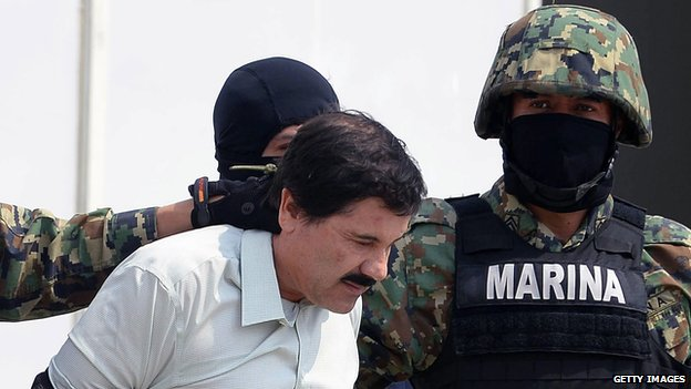Mexican drug trafficker Joaquin Guzman is escorted by marines as he is presented to the press on 22 February, 2014