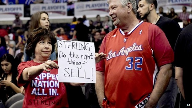 A LA Clippers fan holds a sign calling for owner Donald Sterling to sell the team - 29 April 2014