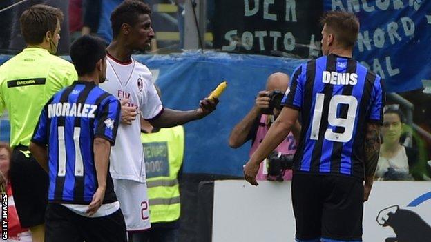 Kevin Constant holding a banana thrown at him during AC Milan's match against Atalanta